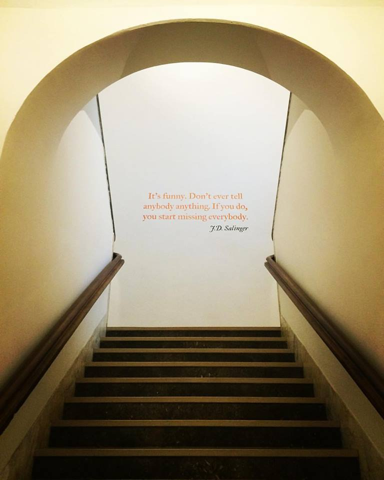 A staircase leads to walls painted with quotes from J. D. Salinger at Scuola Holden.